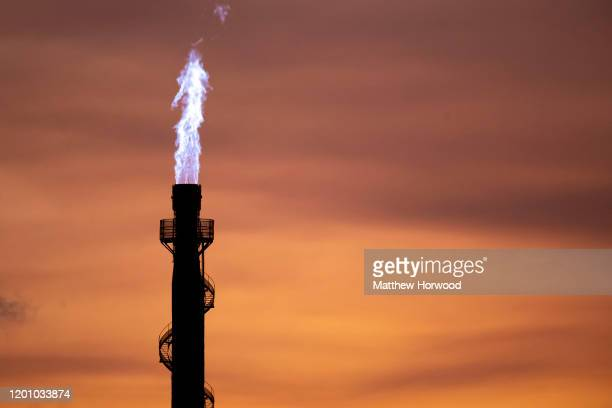 Closeup of flames coming out of a chimney at Tata Steel at sunset on January 21, 2020 in Port Talbot, United Kingdom.