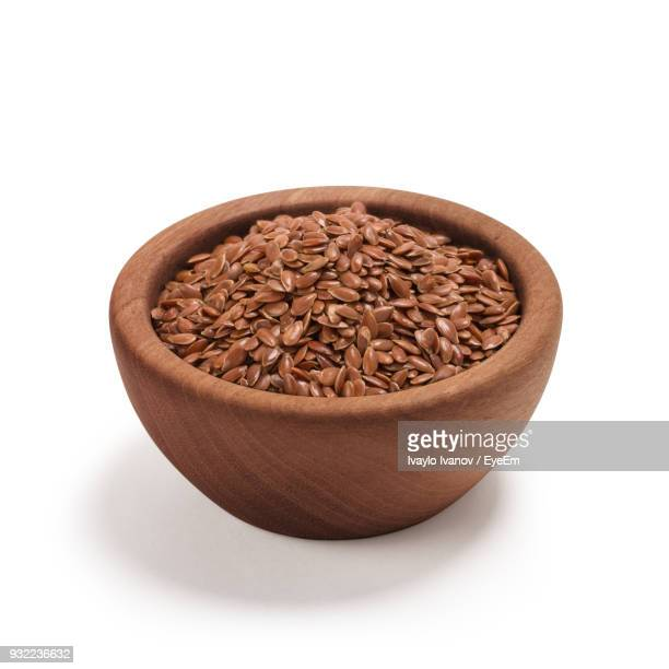 close-up of flax seeds in bowl against white background - flax seed stock pictures, royalty-free photos & images