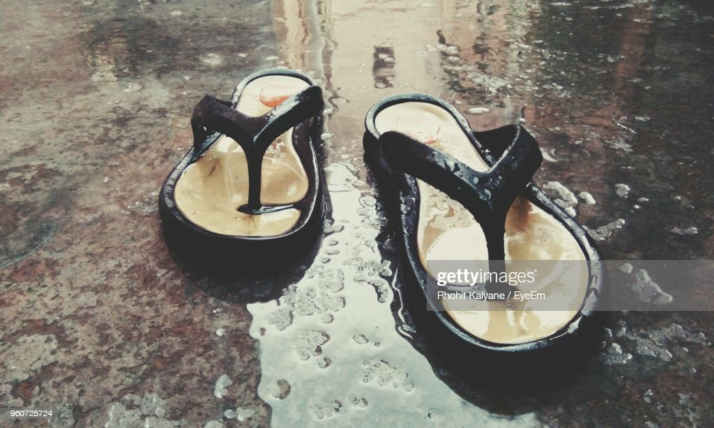 4c31c6099947cf Close-Up Of Flip-Flops On Wet Road   Stock Photo