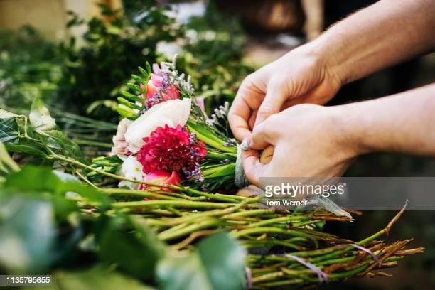 close-up of florist preparing flowers for bouquet - フラワーアレンジメント ストックフォトと画像