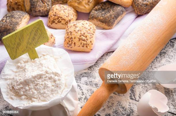 Close-Up Of Flour By Bread And Rolling Pin On Table