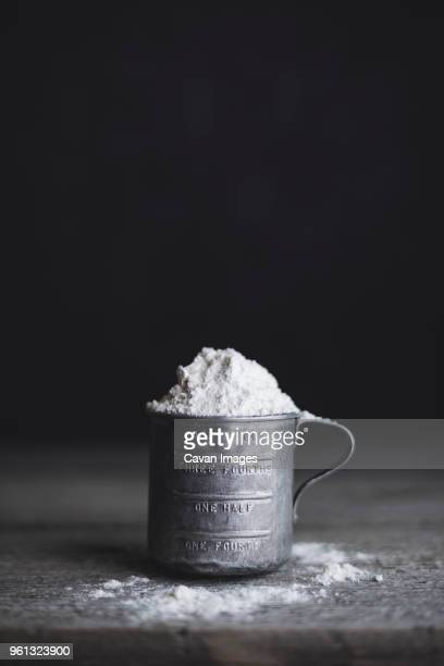 close-up of flour in measuring cup on table - measuring cup stock pictures, royalty-free photos & images