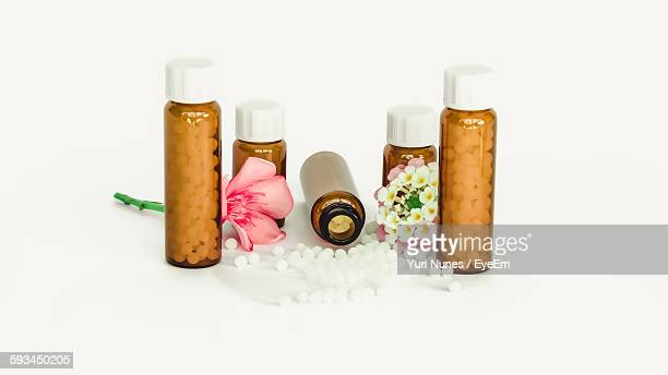 close-up of flower and medicine against white background - homeopathic medicine stock photos and pictures
