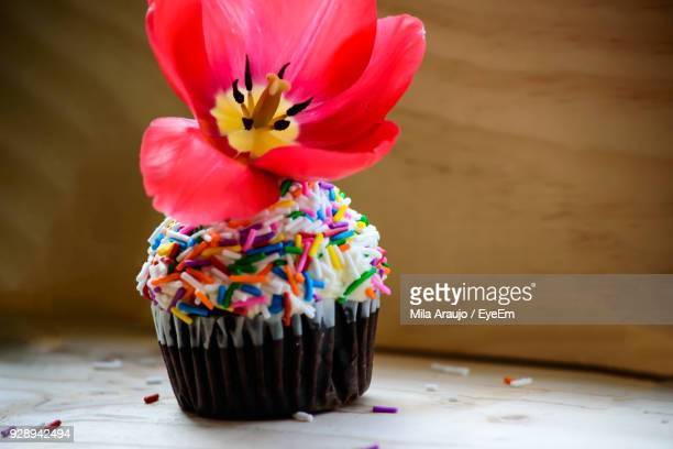 Close-Up Of Flower On Cupcakes Over Table