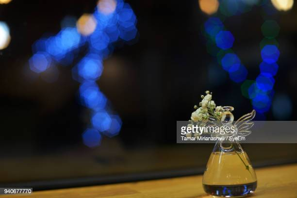 Close-Up Of Flower Vase Illuminated On Table Against Defocused Lights