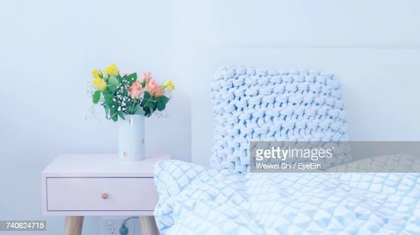 Close-Up Of Flower Vase On Night Table In Bedroom