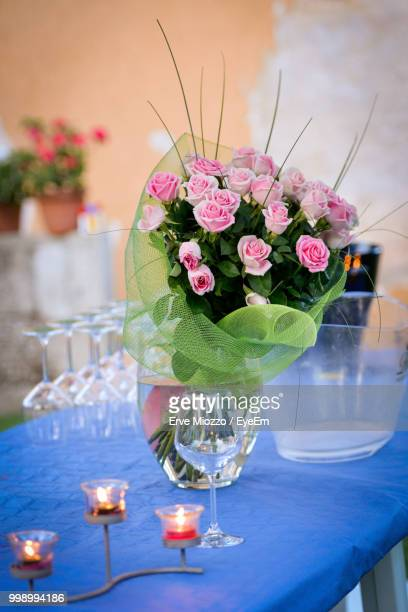 Close-Up Of Flower Vase With Candles And Wineglass On Table
