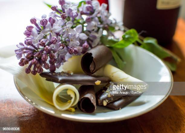 Close-Up Of Flower With Chocolate In Plate On Table