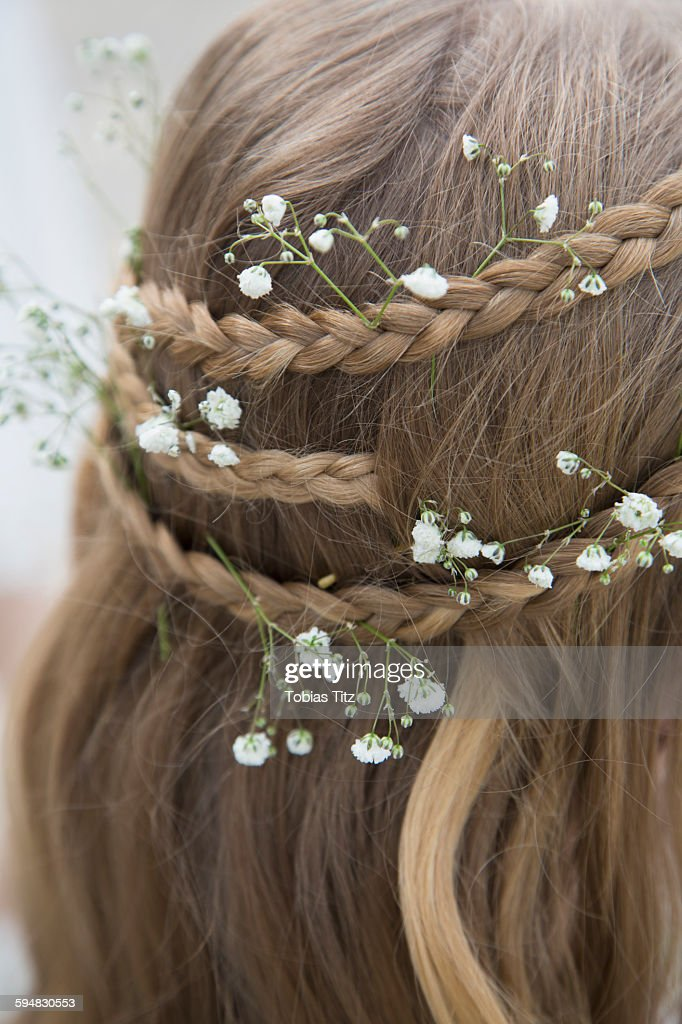 Close-up of flowers in braided hair : Stock Photo