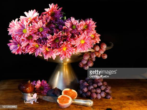 Close-Up Of Flowers In Vase On Table Against Black Background