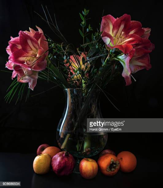 Close-Up Of Flowers In Vase With Fruits On Table Against Black Background