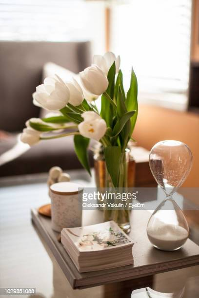 Close-Up Of Flowers In Vase With Picture Frames And Hourglass On Table At Home