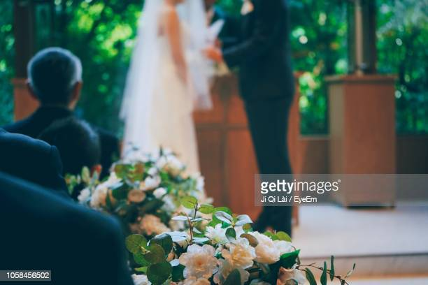 close-up of flowers with bride and groom in background - cerimonia di nozze foto e immagini stock