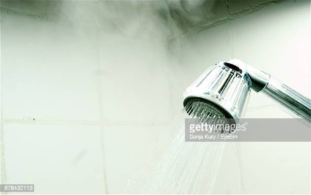 close-up of flowing water from shower faucet with steam in bathroom - steam stock pictures, royalty-free photos & images