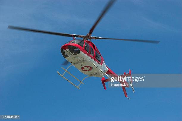 Closeup of flying red helicopter in contrast with blue sky