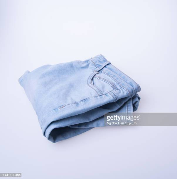 close-up of folded jeans on blue background - trousers stock pictures, royalty-free photos & images