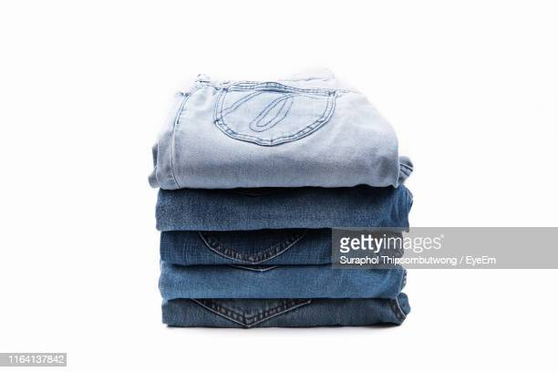 close-up of folded jeans stack against white background - trousers stock pictures, royalty-free photos & images