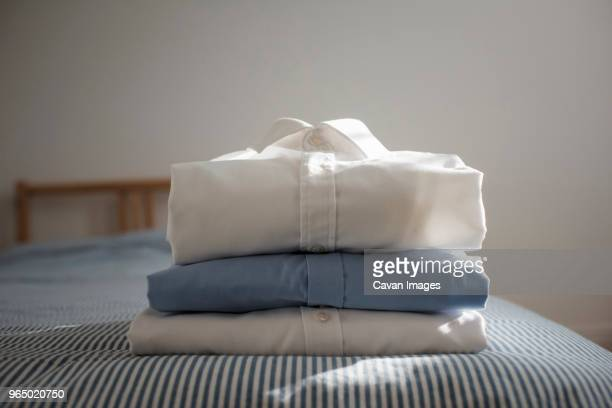 close-up of folded shirts stacked on bed at home - camicia foto e immagini stock