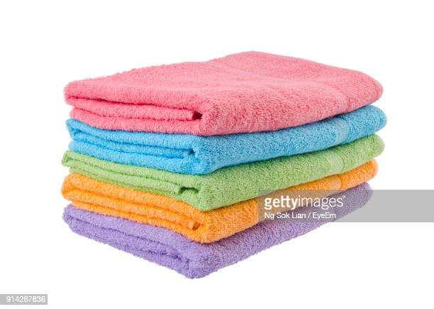 Close-Up Of Folded Towels Stacked Over White Background