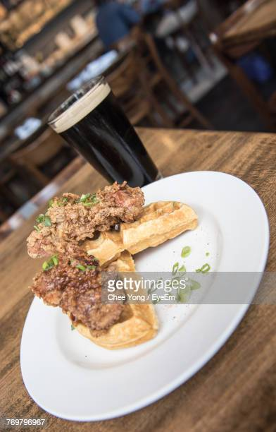 close-up of food and drink on table - chicken and waffles stock photos and pictures