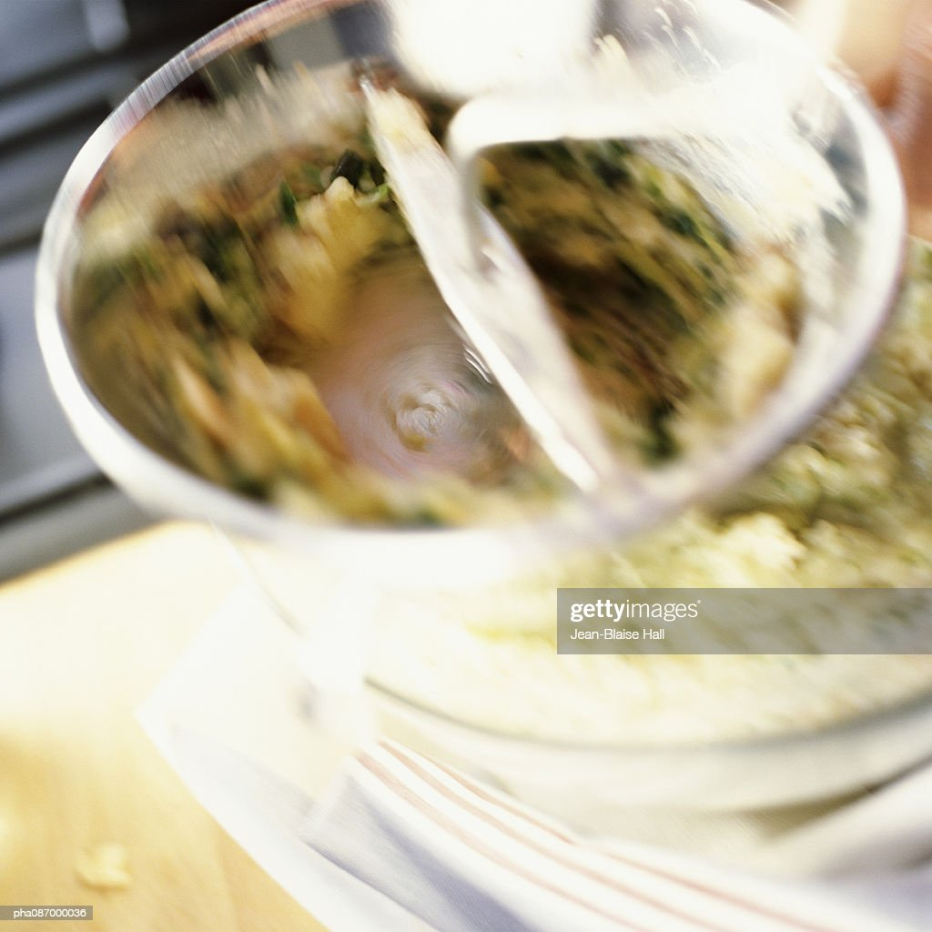 Close-up of food being mixed in bowl, blurry. : Stockfoto