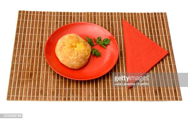 Close-Up Of Food In Plate On Place Mat Over White Background