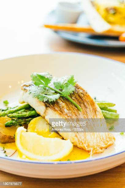 close-up of food in plate on table - フラットフィッシュ ストックフォトと画像