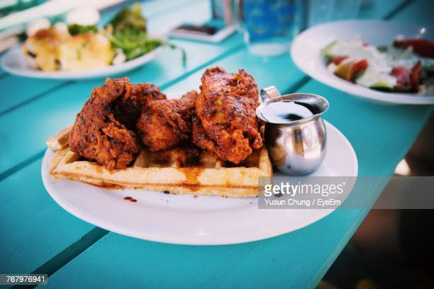 close-up of food in plate on table - chicken and waffles stock photos and pictures