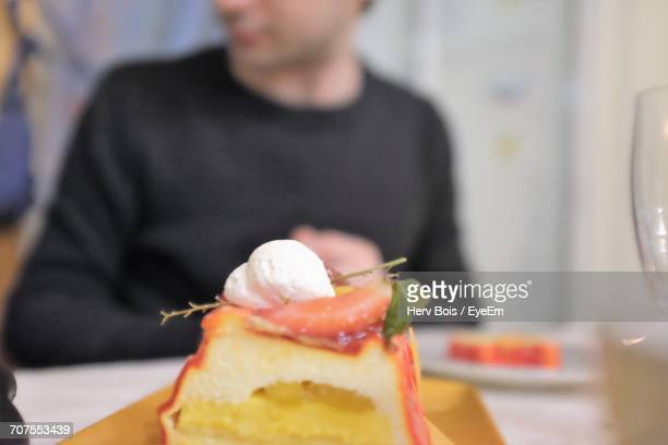 Close-Up Of Food In Tray On Table With Man In Background