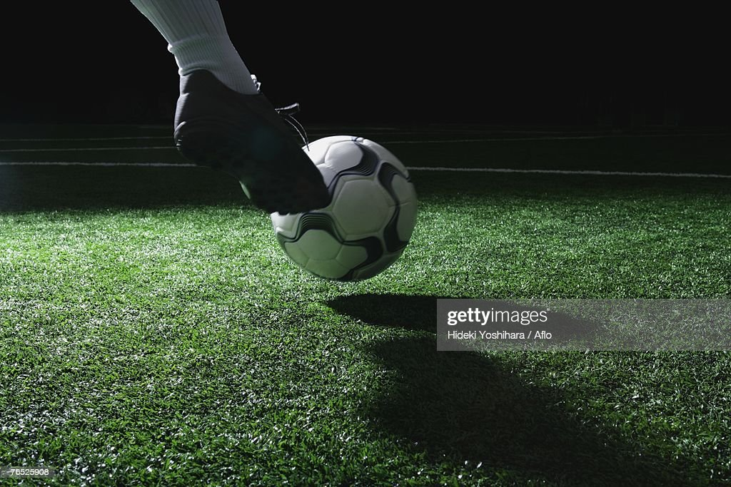 Close-up of foot kicking soccer ball : Photo