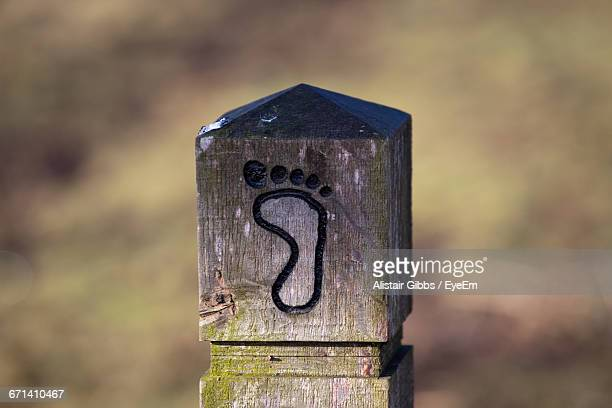Close-Up Of Footpath Sign On Wooden Post