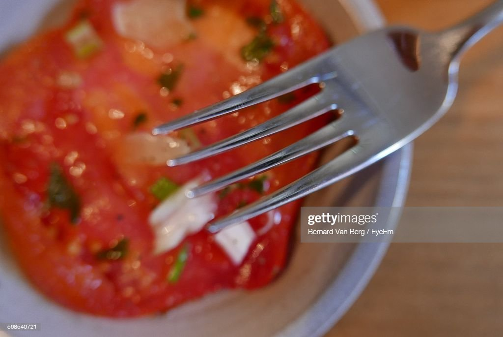 Close-Up Of Fork Against Tomato Salad : Stock Photo