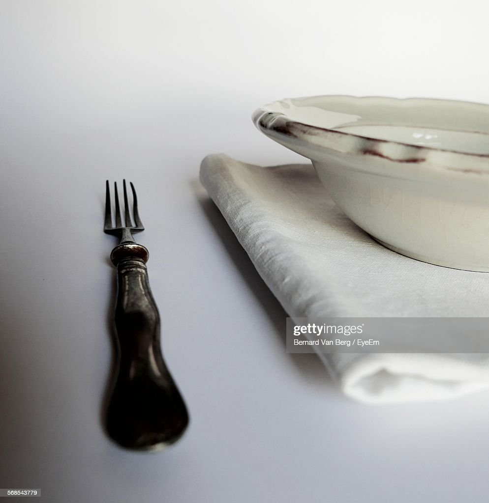 Close-Up Of Fork With Napkin And Bowl On Table : Stock Photo