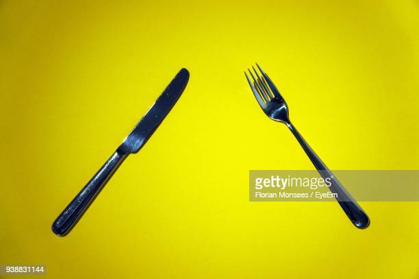 Close-Up Of Fork With Table Knife On Green Background