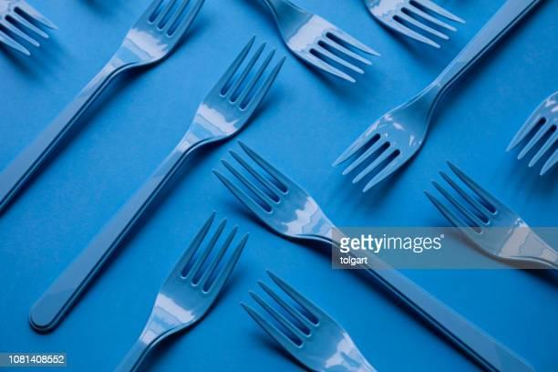 nahaufnahme von gabeln auf blauem hintergrund - küchenbedarf stock-fotos und bilder