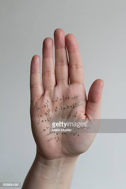 Close-up of formulas written on mans hand against gray background