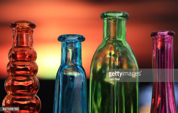 Close-up of four bottles of different shapes and colors against sunset sky