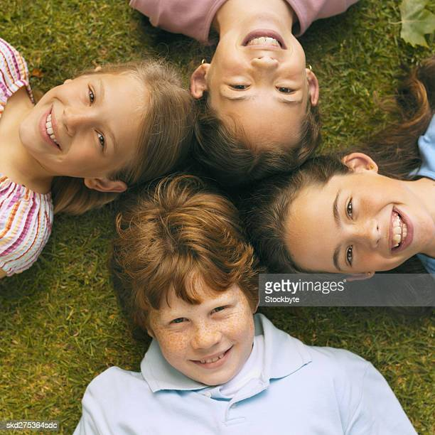 Close-up of four children lying on grass with heads together (8-12)