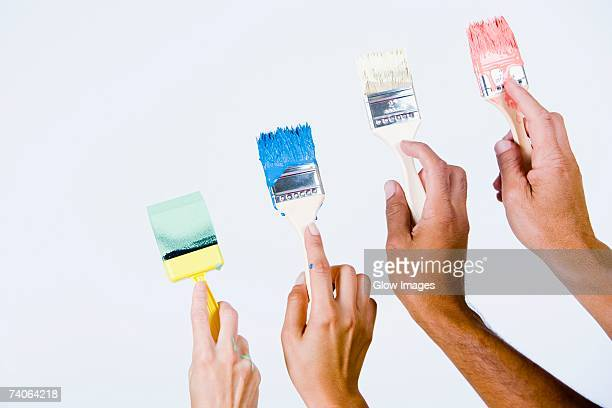 Close-up of four people's hands holding paintbrushes