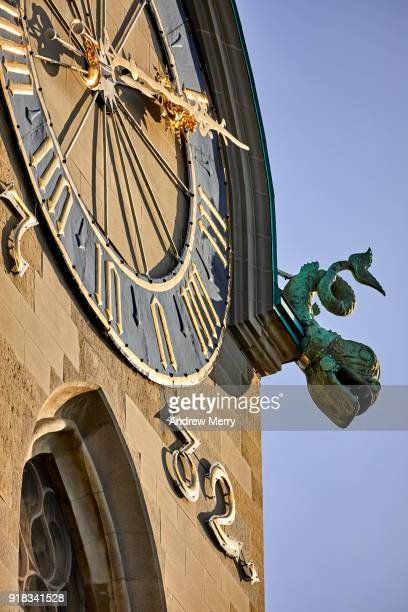 Close-up of Fraumunster Church clock face and gargoyle with blue sky, Zurich, Switzerland