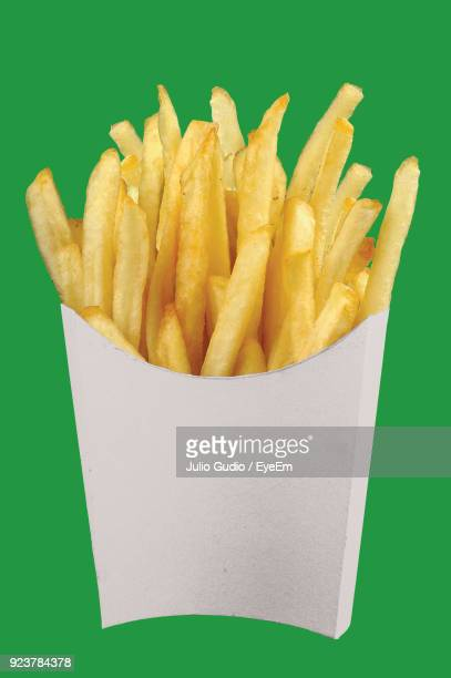 Close-Up Of French Fries On Green Background