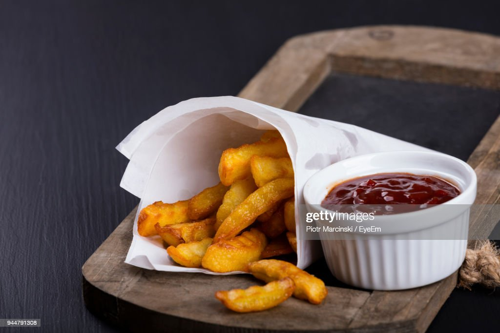 Close-Up Of French Fries With Dip On Cutting Board On Table : Stock Photo