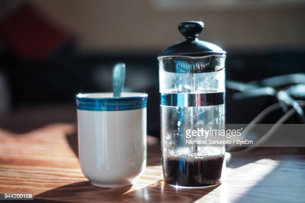 Close-Up Of French Press By Mug On Table