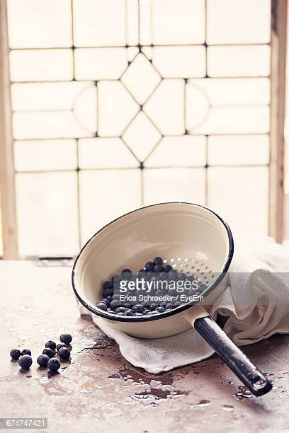 Close-Up Of Fresh Blueberries In Strainer On Table In Kitchen Against Window