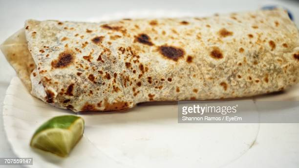 close-up of fresh burrito with lemon piece served in plate - burrito stock pictures, royalty-free photos & images