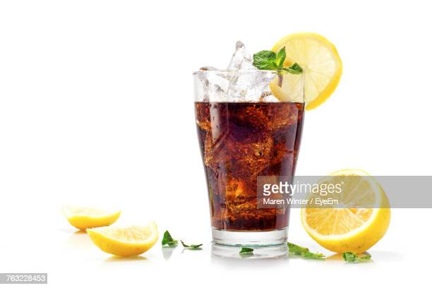 close-up of fresh drink and lemon slices over white background - coca cola fotografías e imágenes de stock