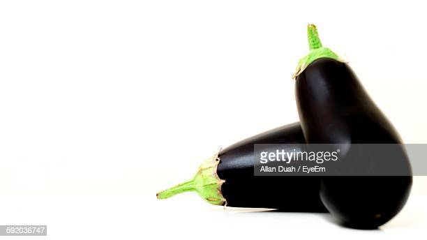 Close-Up Of Fresh Eggplants Against White Background