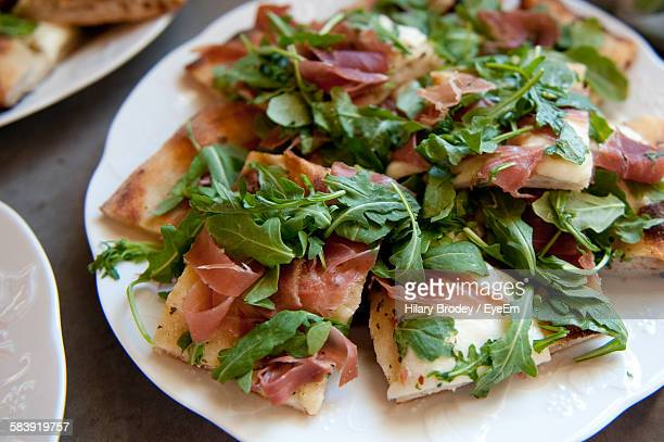 close-up of fresh flatbread prosciutto pizza served in plate - prosciutto stock photos and pictures