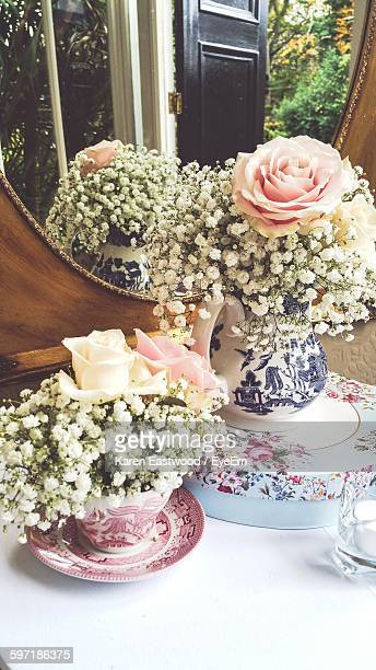 Close-Up Of Fresh Flowers In Porcelain Pots On Table Against Mirror