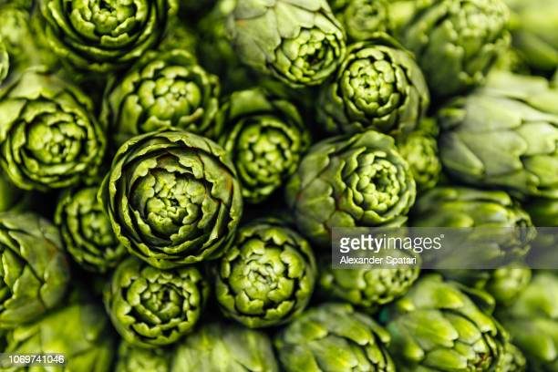 close-up of fresh green artichokes - food and drink stock pictures, royalty-free photos & images